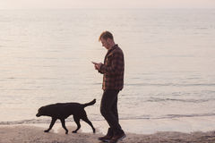 Man walk with dog and texting on cellphone. Young caucasian male walking with dog on the morning beach, sunset on the sea or ocean and man with black labrador Royalty Free Stock Photography