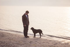 Man walk with dog. Young caucasian male walking with dog on the morning beach, sunset on the sea or ocean and man with black labrador puppy Royalty Free Stock Images