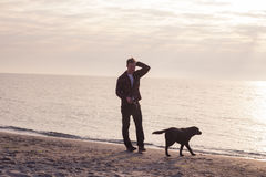 Man walk with dog. Young caucasian male walking with dog on the morning beach, sunset on the sea or ocean and man with black labrador puppy Stock Images