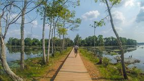 A Man walk on the path through the Great Lake at Angkor Thom Temple royalty free stock photo
