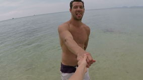 Man walk in sea water holding hand talking action camera pov of young couple on seaside stock video footage