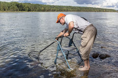 Man with a walker standing in water fishing. Man wearing an orange hat with a walker fiching Royalty Free Stock Images