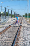Man walking across the railroad tracks Royalty Free Stock Image