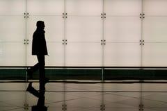 Man walking in airport. Man walking through an airport terminal royalty free stock images