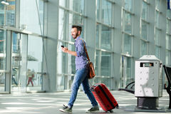 Man walking at airport with suitcase and mobile phone. Full length side portrait of man walking at airport with suitcase and mobile phone Royalty Free Stock Image