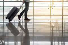 Man walking in the airport terminal with luggage. Reflection of half male body walking in the airport terminal with suitcase luggage, travel background with copy Stock Image