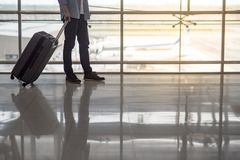 Man walking in the airport terminal with luggage. Reflection of half male body walking in the airport terminal with suitcase luggage, travel background with copy Royalty Free Stock Photo