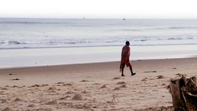 Man walking alone on the beach stock video footage