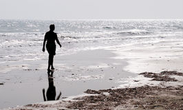 Man walking alone  in the beach. Unrecognized Silhouette of a man walking alone on an empty beach  early in the morning Stock Photos