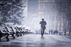 A man walking alone in a cold winter talking on the phone. While it is still snowing Stock Photo