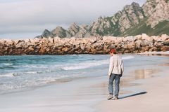 Man walking alone on empty beach traveling in Norway stock image
