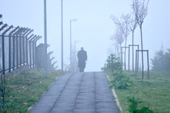 Man walking alone in foggy weather Stock Images