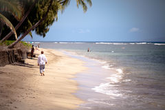 Man Walking alone on a Hawaii Beach Stock Photo