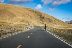 A man walking alone on highway with mountain and blue sky. A man walking alone on highway with mountain and blue sky Stock Photo