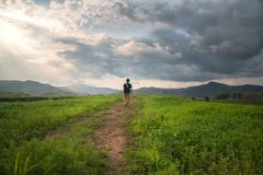 A man walking alone on the road with dramatic sky. View of a man walking alone on the road with dramatic sky Royalty Free Stock Photos