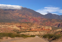 Man walking alone on a sand road with colorful background. Driving through El Cayafate is a feast for the eye stock image
