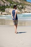 Man walking alone on secluded beach with diary Stock Photography