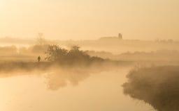 Man walking along banks of river on misty morning Stock Photo