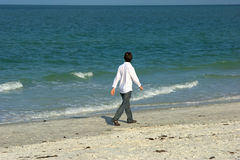 Man walking along the beach royalty free stock photo