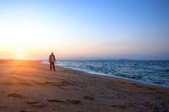 Man walking along the beach during a beautiful sunset relaxation time Stock Photo