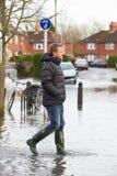 Man Walking Along Flooded Urban Street Stock Images
