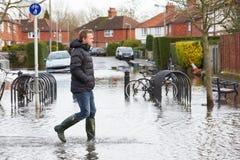 Man Walking Along Flooded Urban Street Royalty Free Stock Photo