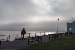 Man Walking Along Misty Promenade at Southwold, Suffolk, UK Royalty Free Stock Photos