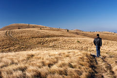 Man walking along mountain path Stock Photos