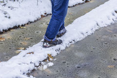 Man walking along a narrow path perilous winter at wet weather Stock Image