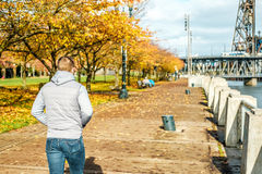 Man walking along the riverwalk in Portland city at autumn Royalty Free Stock Photos