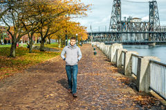 Man walking along the riverwalk in Portland city at autumn Stock Photo