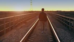 A man walking away at sunset