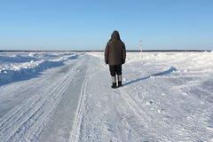 Man walking along a road of ice on the frozen reservoir Royalty Free Stock Image