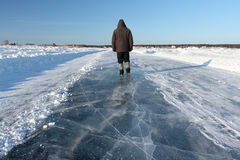 Man walking along a road of ice on the frozen reservoir Stock Images