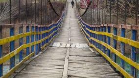 Man is walking along on a rope suspension bridge stock video footage