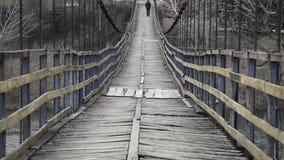Man is walking along on a rope suspension bridge stock footage