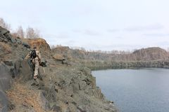 Man walking along the steep bank of a flooded quarry. Man with a backpack walking along the steep bank of a flooded quarry, Toguchinsky district, Siberia, Russia royalty free stock photos
