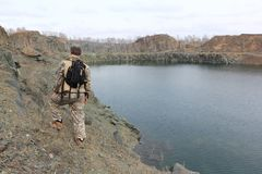 Man walking along the steep bank of a flooded quarry. Man with a backpack walking along the steep bank of a flooded quarry, Toguchinsky district, Siberia, Russia royalty free stock images