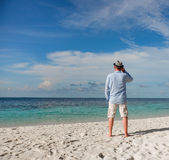 Man walking along a tropical beach in the Maldives. Royalty Free Stock Photography