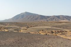 Man walking through an amazing volcanic landscape in Timanfaya national park, Lanzarote, Canary Islands stock photos