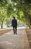 A man walking around a park way unique photo. A man wearing black suits walking around a park way unique photo royalty free stock photo