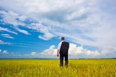 Man walking away. Through the filed Stock Photo