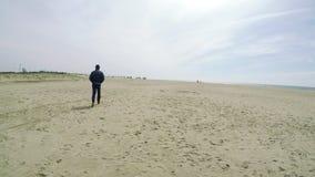 Man walking away on a beach stock video
