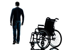 Man walking away from wheelchair silhouette Stock Photo