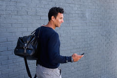 Man walking with bag and mobile phone. Portrait from behind of man walking with bag and mobile phone Royalty Free Stock Photos