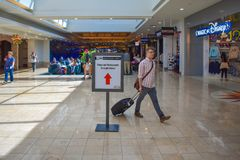 Man walking with baggage close to store area at Orlando International Airport  3 royalty free stock image
