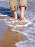 Man walking barefood on the beach. Male feet with rolled up pants wading on the shoreline Stock Photos