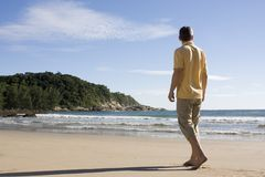Man walking barefoot on a tropical beach Royalty Free Stock Photo