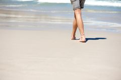 Man walking barefoot on vacation at the beach Stock Photos