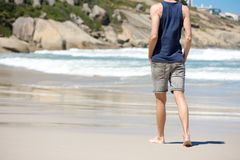 Man walking barefoot on white sand beach Royalty Free Stock Images